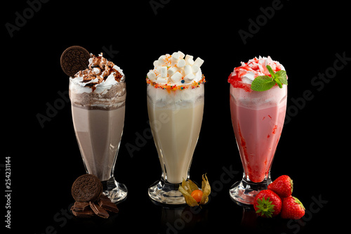 Fotografie, Obraz Three glasses of colorful milkshake cocktails - chocolate, strawberry and vanilla decorated with fresh berries and mint isolated at black background