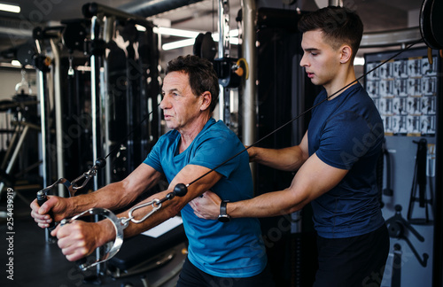 A senior man with a young trainer doing strength workout exercise in gym Fototapet