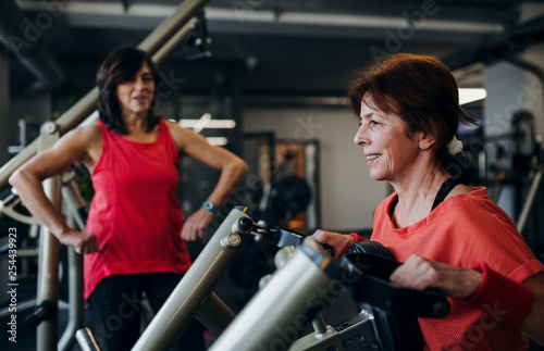 Photo Two cheerful senior women in gym doing strength workout exercise.
