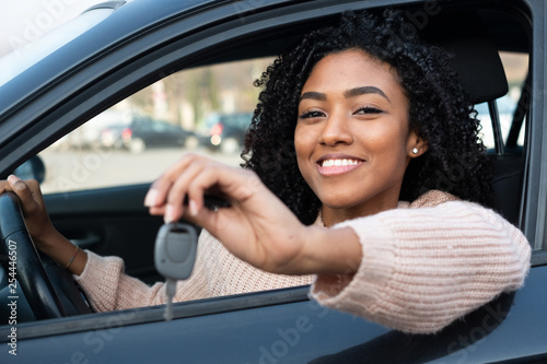 Canvas Print Happy young woman learning to drive car