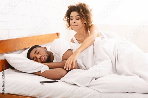 Fotografia Suspicious wife checking her sleeping husband cellphone in bed
