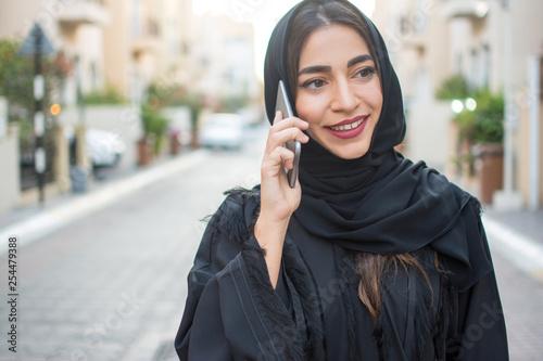 Slika na platnu Portrait of beautiful smiling arab woman talking on mobile phone on the street