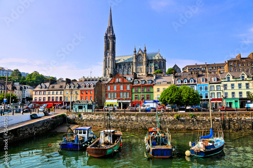 Canvas Print Colorful buildings and old boats with cathedral in background in the harbor of C