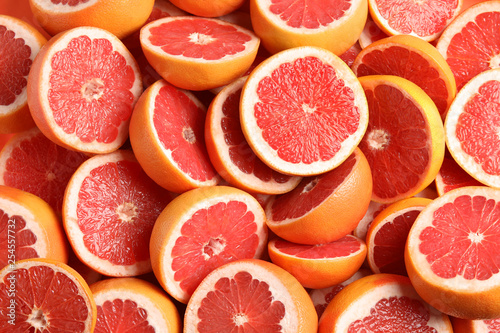 Fotografie, Tablou Many sliced fresh grapefruits as background, top view