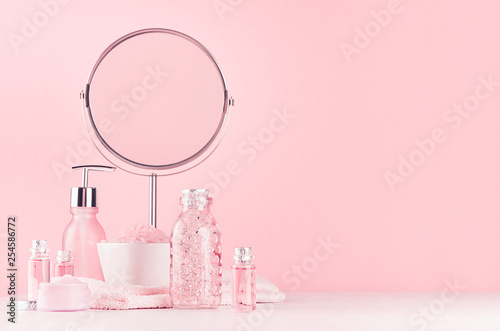 Tableau sur Toile Girlish cute bathroom interior in pastel pink color - cosmetic products for skin and body care and round mirror on soft white wood board, copy space