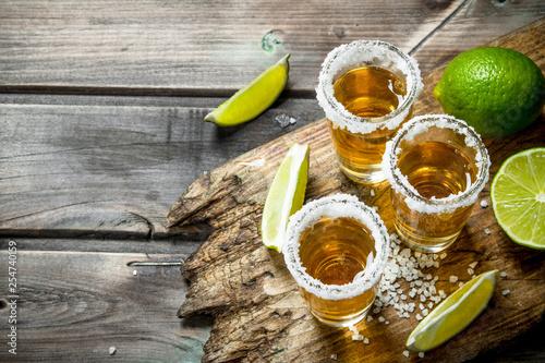 Fototapeta Tequila in a shot glass of salt on the cutting Board.