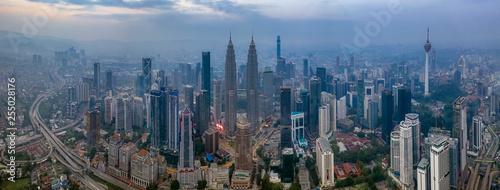 Fototapeta premium Kuala Lumpur, Malezja - 9 marca 2019: Dramatyczne zdjęcie panoramiczne z lotu ptaka panoramę miasta Kuala Lumpur podczas mglistego wschodu słońca.