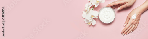 Young woman moisturizes her hand with cosmetic cream lotion opened container with cream body milk White Phalaenopsis orchid flowers on pink background Flat lay top view minimalism style Beauty concept