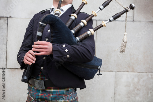 Scottish bagpiper dressed in traditional dress performing on the street Fototapeta