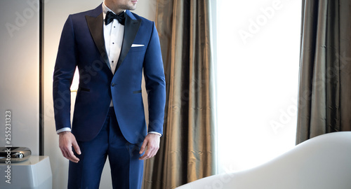 Photo Man model in expensive custom tailored blue tuxedo, suit standing and posing ind