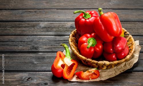 Fotografija Ripe red sweet peppers in a basket on paper.