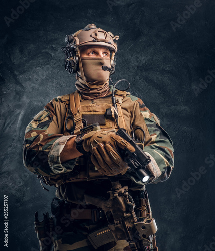 Canvas-taulu Elite unit, special forces soldier in camouflage uniform holding a gun with a flashlight and looking sideways
