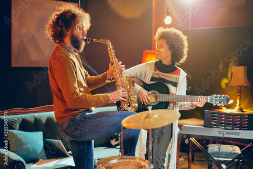 Fotografie, Obraz Mixed race woman playing acoustic guitar while man playing saxophone
