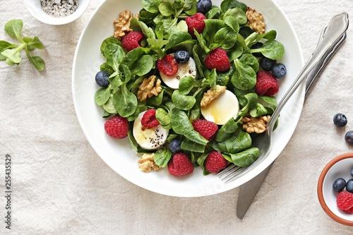 Green salad with goat cheese, walnuts,  fresh berries and lemon honey dressing Fototapeta