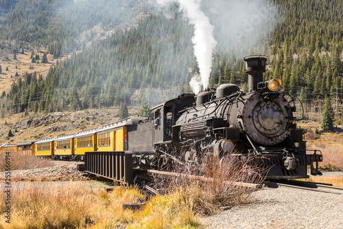 Fototapeta Vintage steam train with yellow wagons going uphill in mountain area
