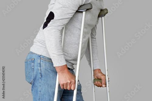 Man on crutches on a gray background Fototapeta