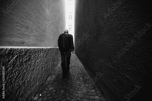 Fototapeta A man in black walking along a narrow alley toward the light