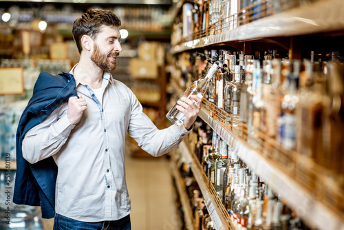 Portrait of a man with a thirst for alcohol, standing near the shelves with stro Fototapeta