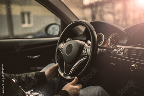 Fotografie, Tablou driver's hands hold the steering wheel of a modern car while waiting for a passenger