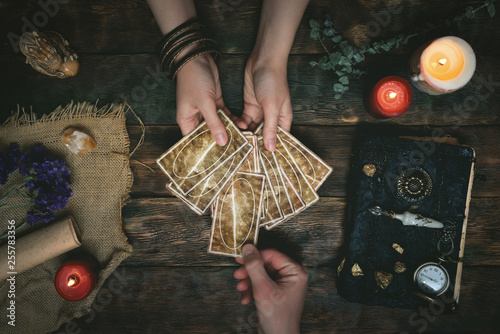 Carta da parati Tarot cards, magic book and fortune teller hands on a wooden table background