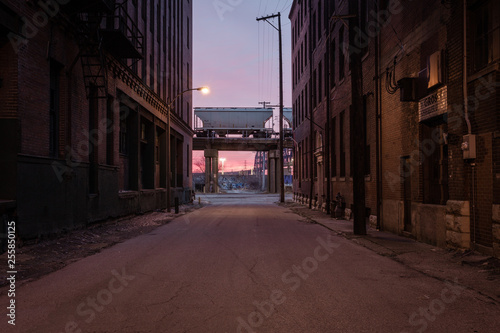 Looking down a street with vintage brick buildings at a freight train car at rest