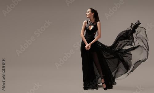 Fotografiet Beautiful woman in luxury evening black dress. Gray background.