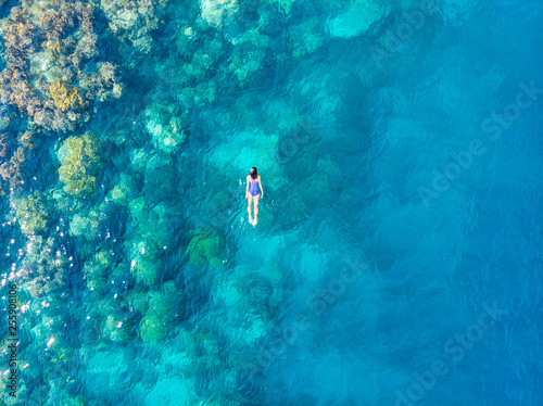 Fotografia Aerial top down people snorkeling on coral reef tropical caribbean sea, turquoise blue water