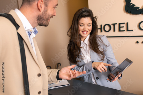 Wallpaper Mural Young business man check-in in hotel, smiling female receptionist behind the hotel counter showing him available rooms on tablet