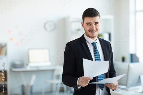Fotografija Smiling young successful banker in elegant suit looking through financial docume