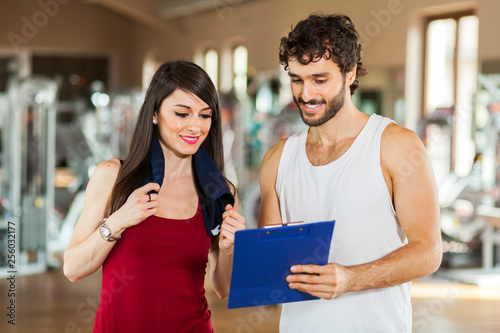 Fotografie, Obraz Handsome personal trainer with his client looking at clipboard at the gym