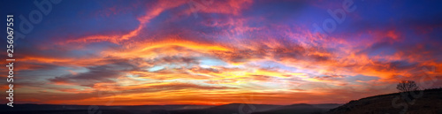 Panorama colorful magnificent sunset in countryside above hills and fields, beauty nature background
