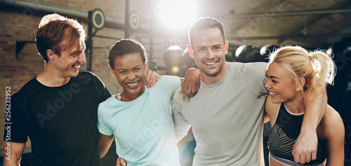 Stampa su Tela Laughing group of diverse friends standing together in a gym