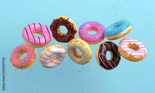 Fotografiet Various decorated donuts in motion falling on blue background