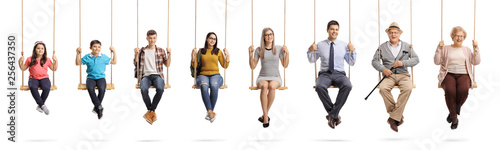 Canvas Print Children, young people and seniors sitting om swings and smiling