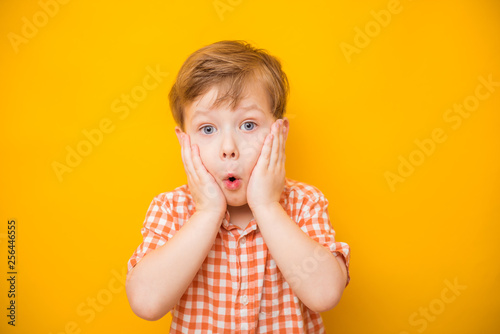 Surprised funny child boy with hands on his cheeks. Yellow background