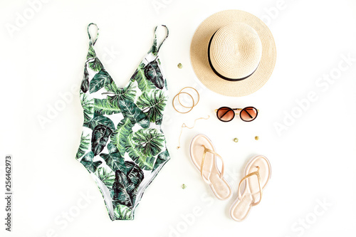 Canvas Print Woman's beach accessories: swimsuit with tropical print, rattan bag, straw hat on white background