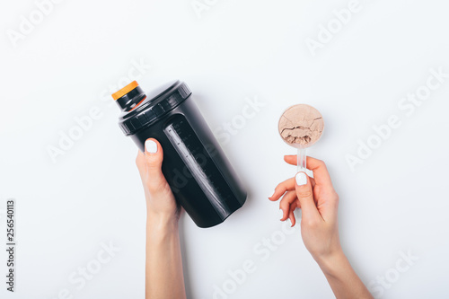 Fotografia Female's hands holding scoop of chocolate protein powder