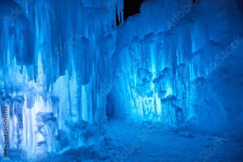 Obraz na plátně Wall of blue icicles on a subzero night after sunset on a lake in Minnesota USA