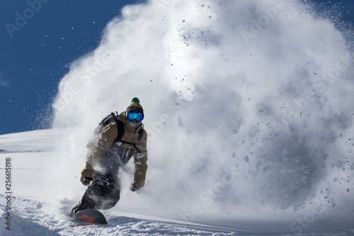 Obraz na płótnie male snowboarder curved and brakes spraying loose deep snow on the freeride slop