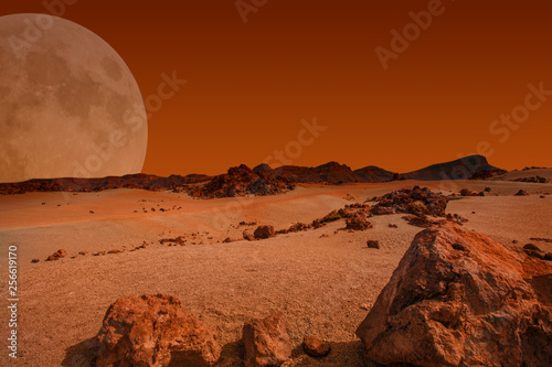 Valokuva Red planet with arid landscape, rocky hills and mountains, and a giant Mars-like moon at the horizon, for space exploration and science fiction backgrounds