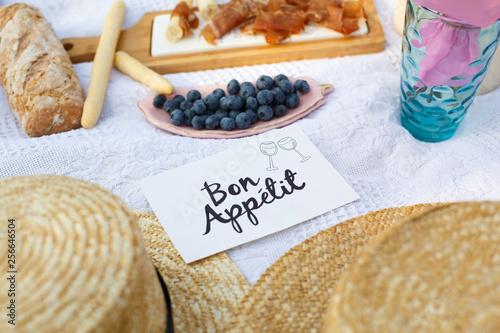 straw hats lay on a white picnic blanket next to nameplate bon apetit bright summer day background Fototapet