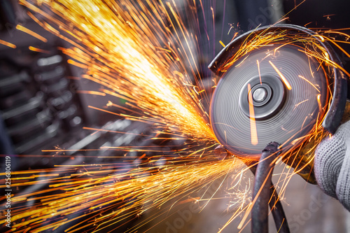 Fotografia, Obraz A close-up of a car mechanic using a metal grinder to cut a car bearing  in an a