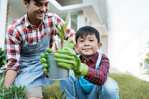 Photo dad and son planting a plant gardening at their house together