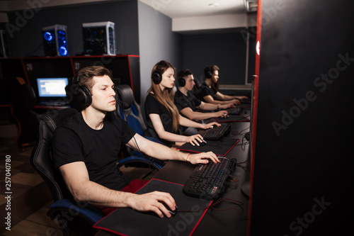 Fotografie, Obraz Young female and male gamers playing video game while spending weekend leisuretime at pc gaming club, focused serious people behind pc monitor at dark room