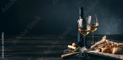 Photographie dinner concept for two. two glasses of white wine, baked fish.