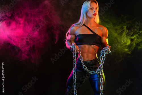 Photo Sporty fit woman bodybuilder, athlete, on background with color smoke holding chains in the hand