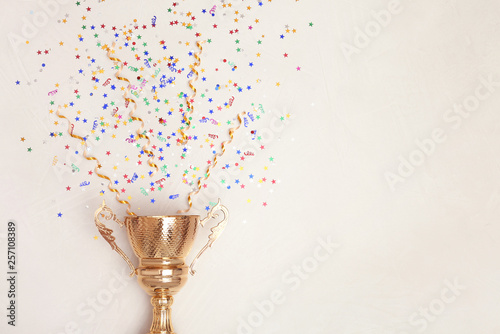 Valokuva Trophy and confetti on light background, top view with space for text