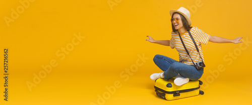 Fotografia Horizontal banner of young tourist girl sitting on suitcase, pretending flying on a plane, isolated on yellow background with copy space