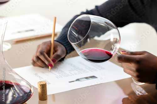 Fotografia Enologist evaluating red wine at wine tasting.