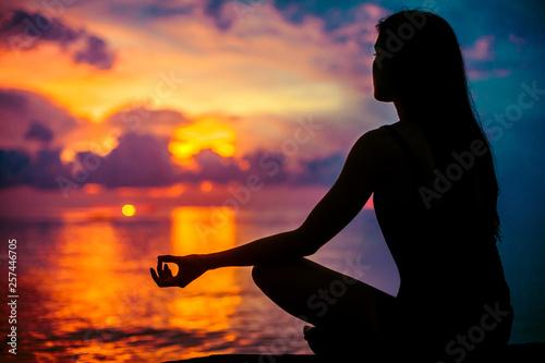 Fotografia Woman meditating, relaxing in yoga pose at sunset, zen meditation